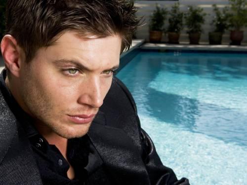 Красивый мужчина в черном у бассейна